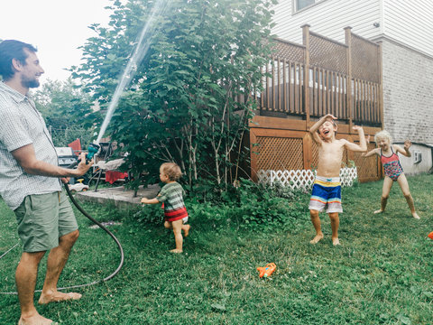 Father man spray shower from hose on kids. Boy girl friends siblings splashing playing under water on backyard on hot summer day. Candid authentic lifestyle funny family moment.