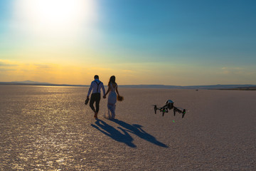 Luxury and futuristic wedding photography and videography. Hovering drone taking pictures of wedding couple at Salt Lake, Sereflikochisar, Turkey.