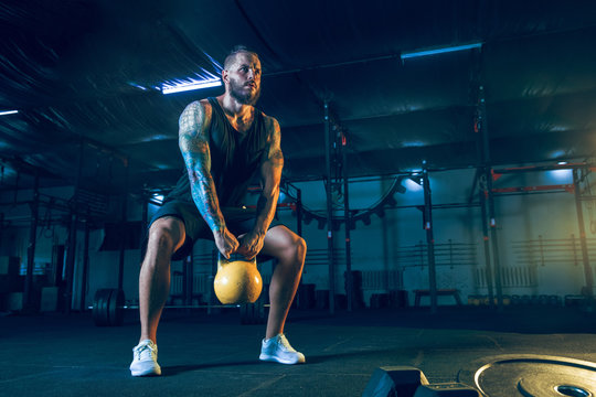 Young healthy man athlete doing exercise with the weights in the gym. Single male model training hard and practicing in squats. Concept of healthy lifestyle, sport, fitness, bodybuilding, crossfit.