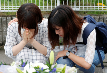 Women pray in front of a row bouquets placed out for victims of the torched Kyoto Animation building in Kyoto