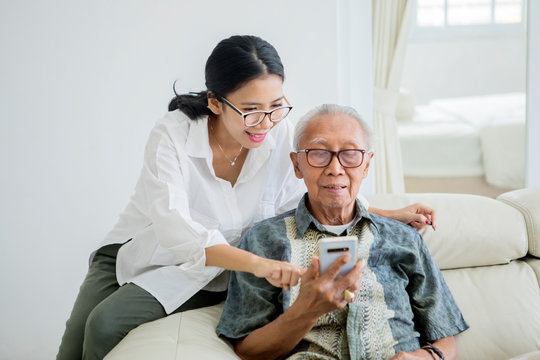 Elderly man using a phone with his daughter