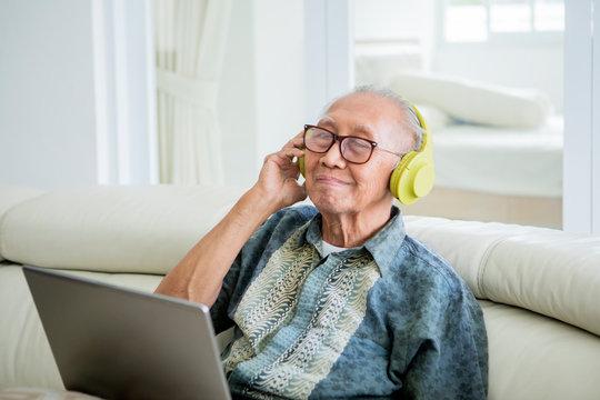 Happy old man enjoying music with headphones