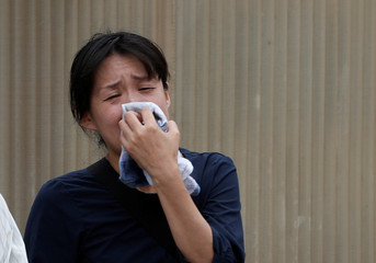 A woman cries as she looks at the torched Kyoto Animation building in Kyoto