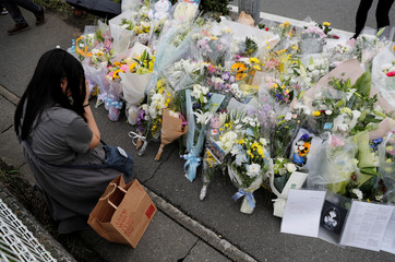 A woman prays in front of a row of flowers placed for victims of the torched Kyoto Animation building in Kyoto