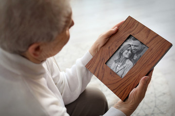 Elderly woman with framed family portrait at home