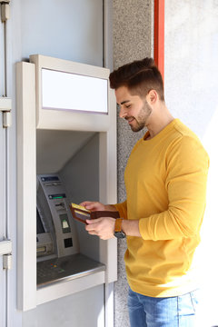 Young man with credit card near modern cash machine outdoors