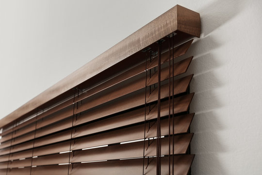 Modern window with closed stylish wooden blinds indoors, closeup view