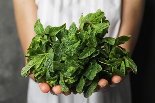 Young woman holding bunch of fresh mint, closeup