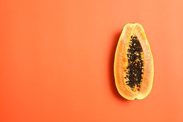 Fototapete - Fresh juicy halved papaya on coral background, top view. Space for text