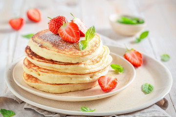 Delicious american pancakes with powdered sugar and sweet strawberries