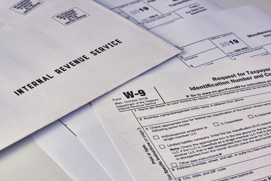 Three mails from the Internal Revenue Service lie on tax Form w-9, 1099-misc, 1099-k on a white background