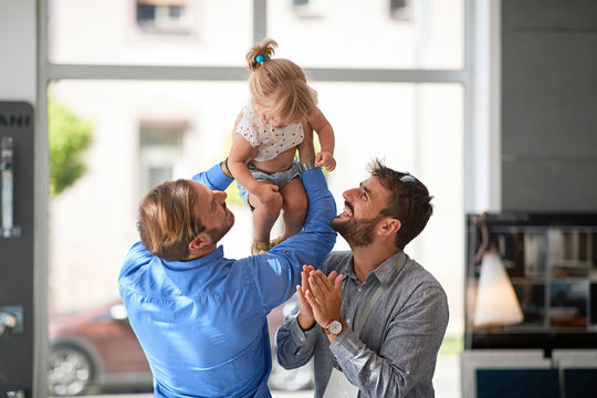 Smiling gay couple with child.