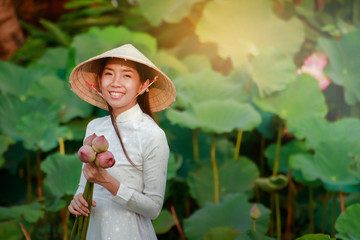 A beautiful girl wearing a Vietnamese dress holds a large lotus flower for offering to the Buddha.