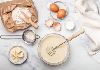 Preparation of dough for home pancakes for Breakfast. Ingredients on the table - wheat flour, eggs, butter, sugar, salt, milk. Selective focus