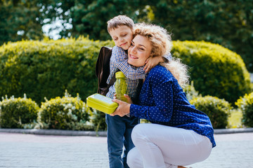 Happy blond curly mother hugging smiling son wearing schoolbag giving him a school lunch box outdoor. Feeling emotions before long goodbye concept.