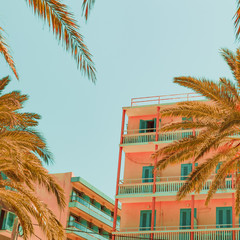 Hotel building and palm trees. Tropical beach style.