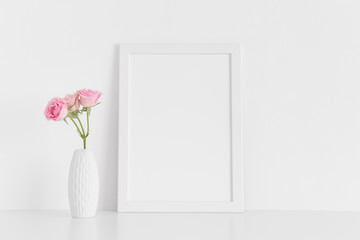 White frame mockup with pink roses in a vase on a white table.Portrait orientation.