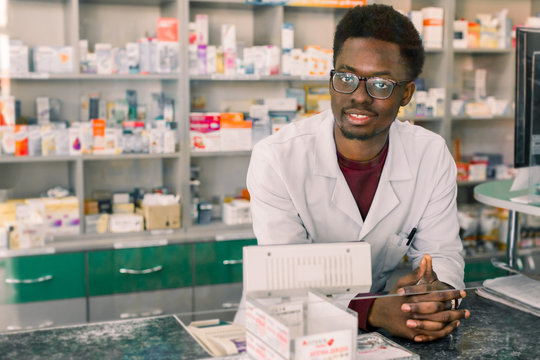 Experienced African American man pharmacist in white coat working in modern pharmacy