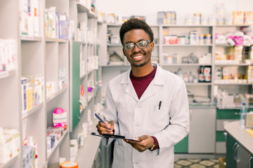 Smiling African American man pharmacist or Chemist Writing On Clipboard While standing in interior of pharmacy
