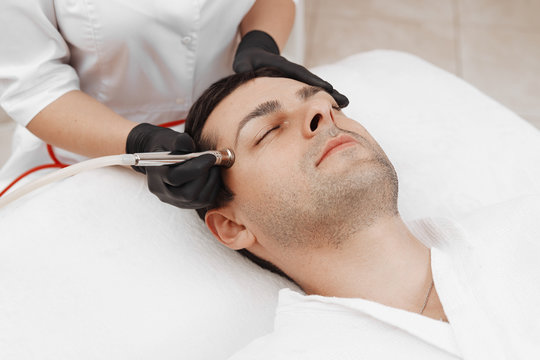 The cosmetologist makes the procedure Microdermabrasion