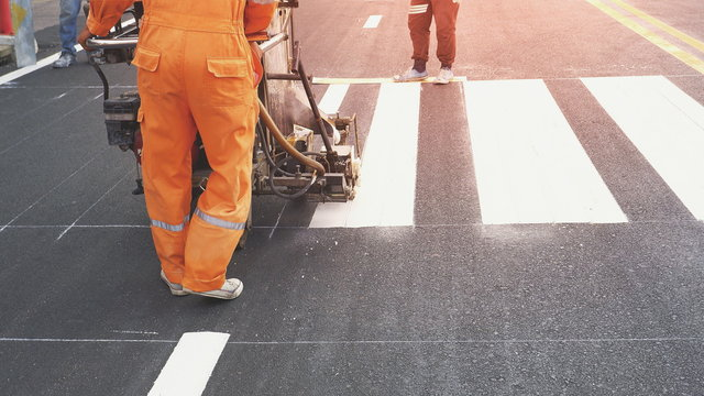 Road workers with thermoplastic spray road marking machine working to paint pedestrian crosswalk on asphalt road surface in the city