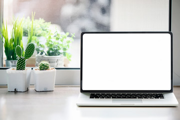 Mockup white blank screen laptop with cactuses flower on wooden table.