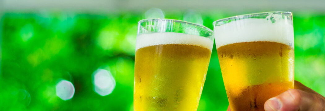 Close-up view of a two glass of beer in hand. Beer glasses clinking at outdoor bar or pub