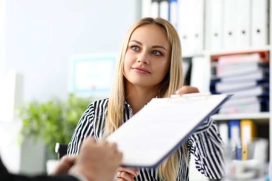 Beautiful smiling female real estate agent offering male visitor document to sign