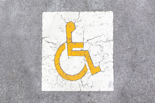 Disable parking painted yellow sign. Handicapped parking spot on the road.