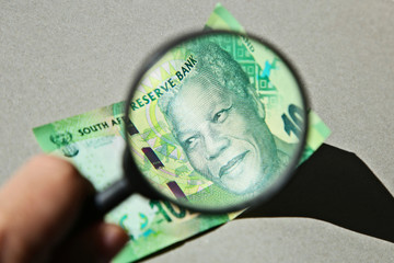 South African money concept image consisting of a magnifying glass and a 10 rand note.