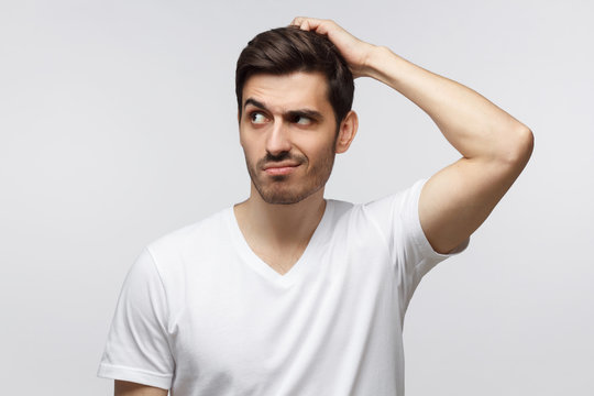 Young doubtful man thinking, scratching his head trying to find solution, isolated on gray background