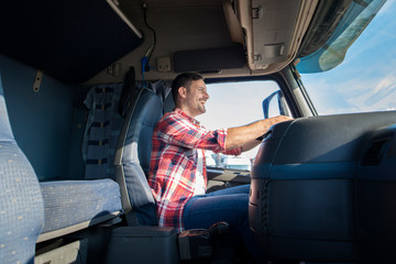 Happy professional middle aged truck driver in casual clothes driving truck on highway. Cabin interior view. Transportation services. Wall mural