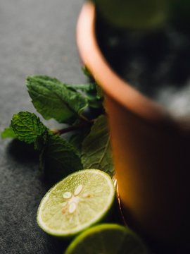 Closeup of lemons and mint leaves near a blurred copper cup