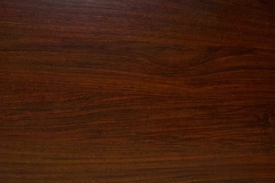Polished wood texture. The background of polished wood texture with a dark amber color