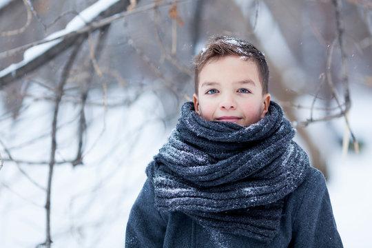 Portrait of happy boy in black coat for walk in winter park, outdoor