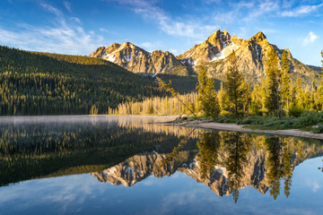 Stanley Lake in the Sawtooth National Forest at sunrise with mountain reflection in water Wall mural