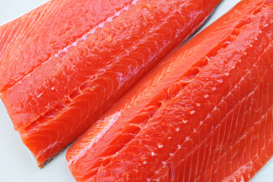 Wild-caught sockeye salmon fillets on a white background.