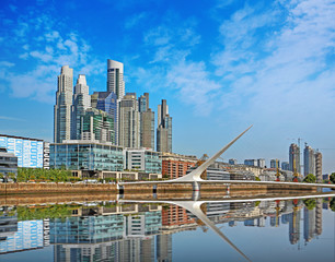 Photo sur Toile Buenos Aires Puente de la Mujer bridge in Buenos Aires and the skyline against a blue summer sky with few white clouds reflecting on the river.