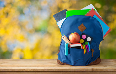 Back to school concept with bag backpack and school supplies on wooden table over autumn bokeh background Wall mural