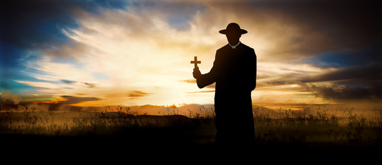 priest on the hill at sunset with the cross
