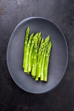 Traditional blanched green asparagus as top view on a cast iron design plate with copy space