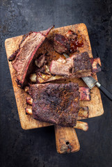 Barbecue sliced chuck beef ribs with hot rub as top view  on a wooden cutting board