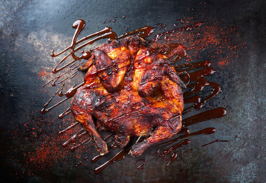 Barbecue spatchcocked barbecue chicken al mattone with hot chili sauce as top view on an old metal sheet