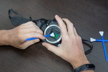 Close-up of camera matrix cleaning, technician pov. Photographer cleaning photocamera light sensor with cleaning swab. Professional photographing equipment care, technology, hobby concept.