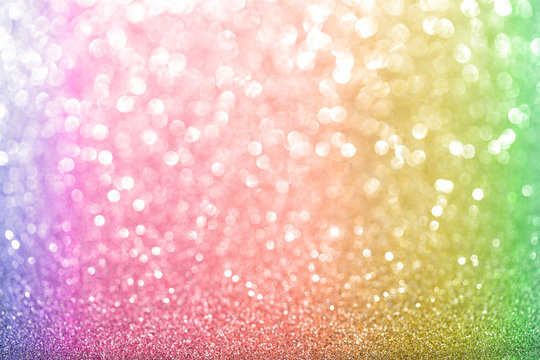 Shiny glitter beautiful multi-colored or rainbow background with white bokeh and glare. Christmas background with sparkle