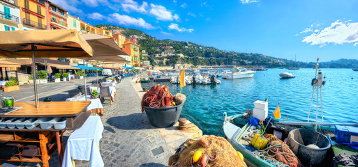 Photo sur Plexiglas Nice Street scene with cafe and fishing boat in resort town Villefranche-sur-Mer. Cote d'Azur, France