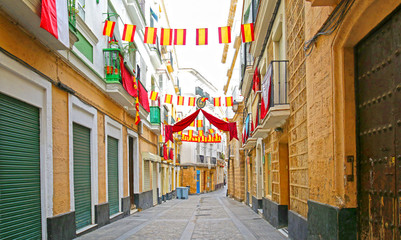 Narrow Old Town Street of Cadiz in the morning, Cobble Stones pavement. Andalusia, Spain.  Colorful Spanish Flags.