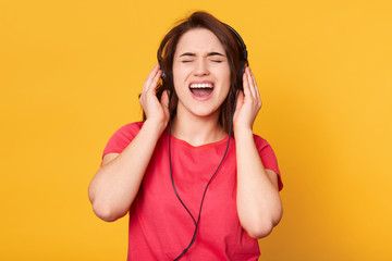 Image of attractive energetic brunette wearing casual red t shirt, having headphones, listening to music, singing, enjoying spending her spare time alone, closing eyes, opening mouth widely.