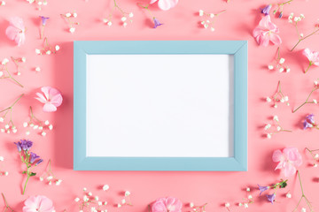 Beautiful flowers composition. Empty photo frame, pink flowers on pastel pink background. Valentines Day, Easter, Birthday, Happy Women's Day, Mother's day. Flat lay, top view, copy space