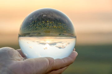 Crystal ball photography - sunset nature landscape, hand holding the ball